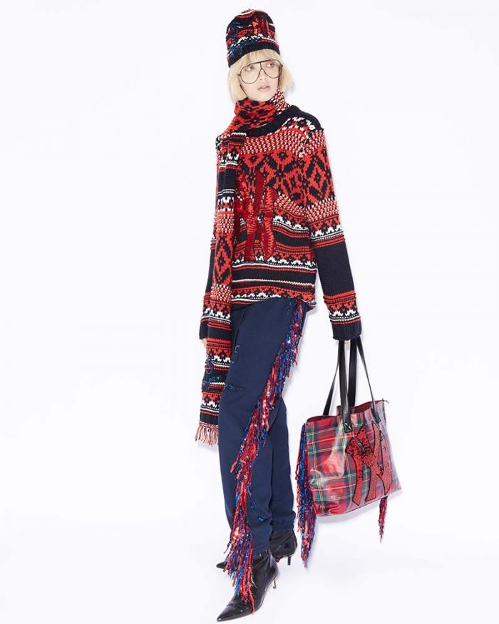Model wearing 5 PROGRESS total look with printed sweater, jeans with fringe detail, knit hat, fringed detail bags