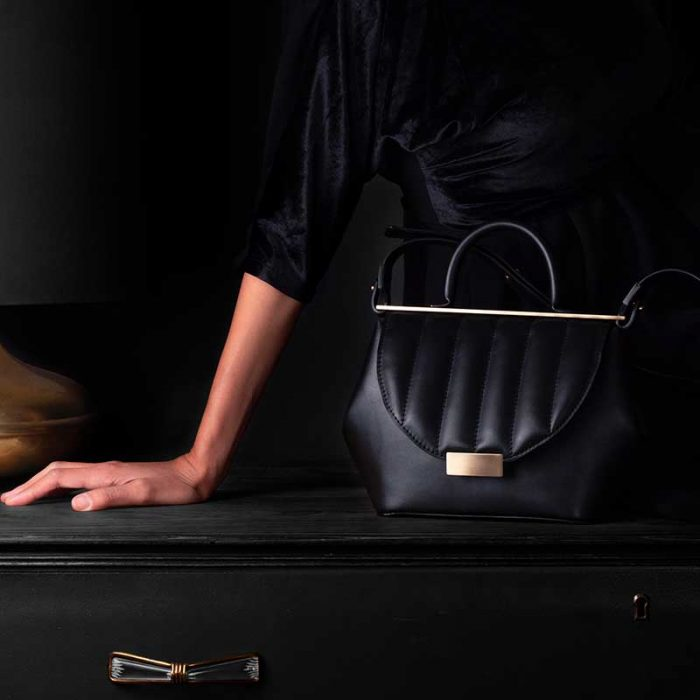 Handbag by Marco Trevisan: small black glossy leather handbag with handle, shoulder strap and golden details