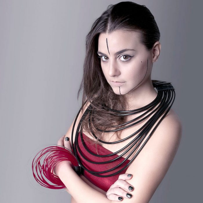 Model wearing a large multi-strand black necklace by Anna Maria Cardillo