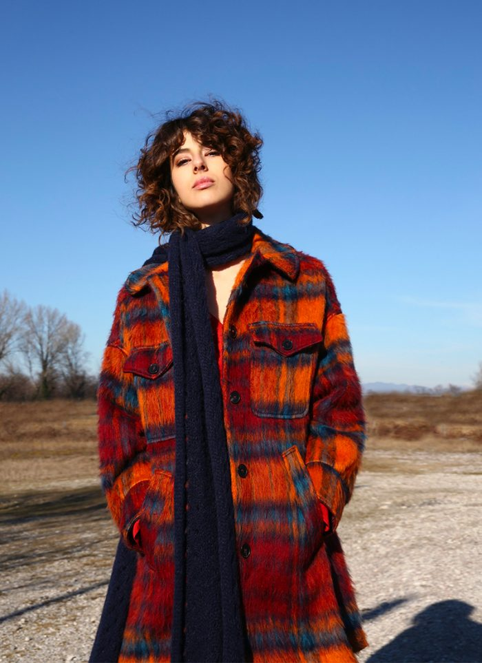 Close-up model with a blue and orange tartan print coat Attic and Barn