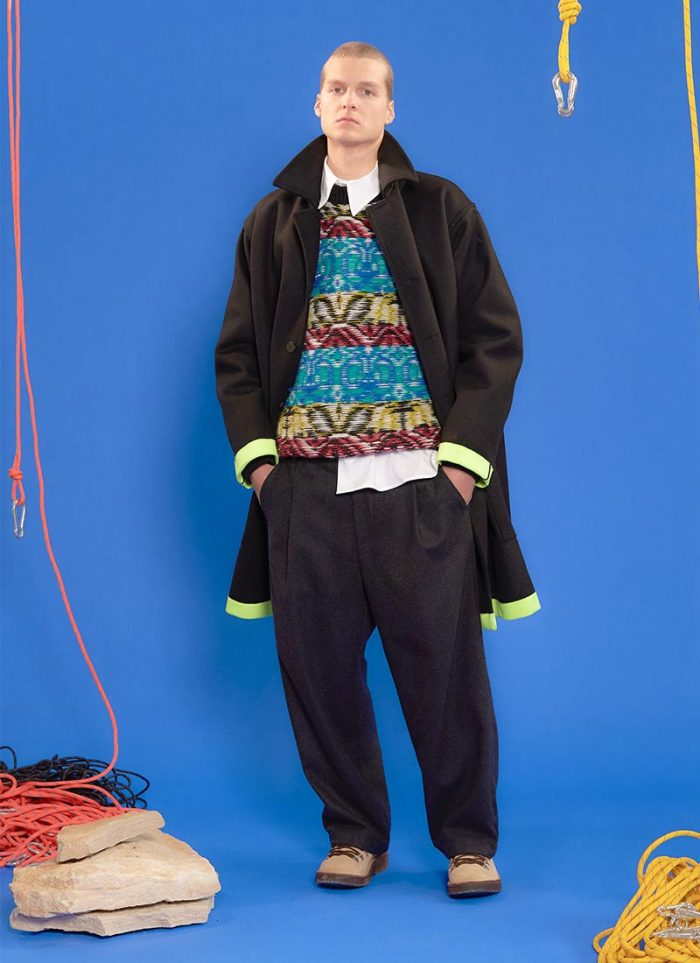 The model wears Bonsai total look with acid green lapels black coat, jacquard colored sweater, over trousers