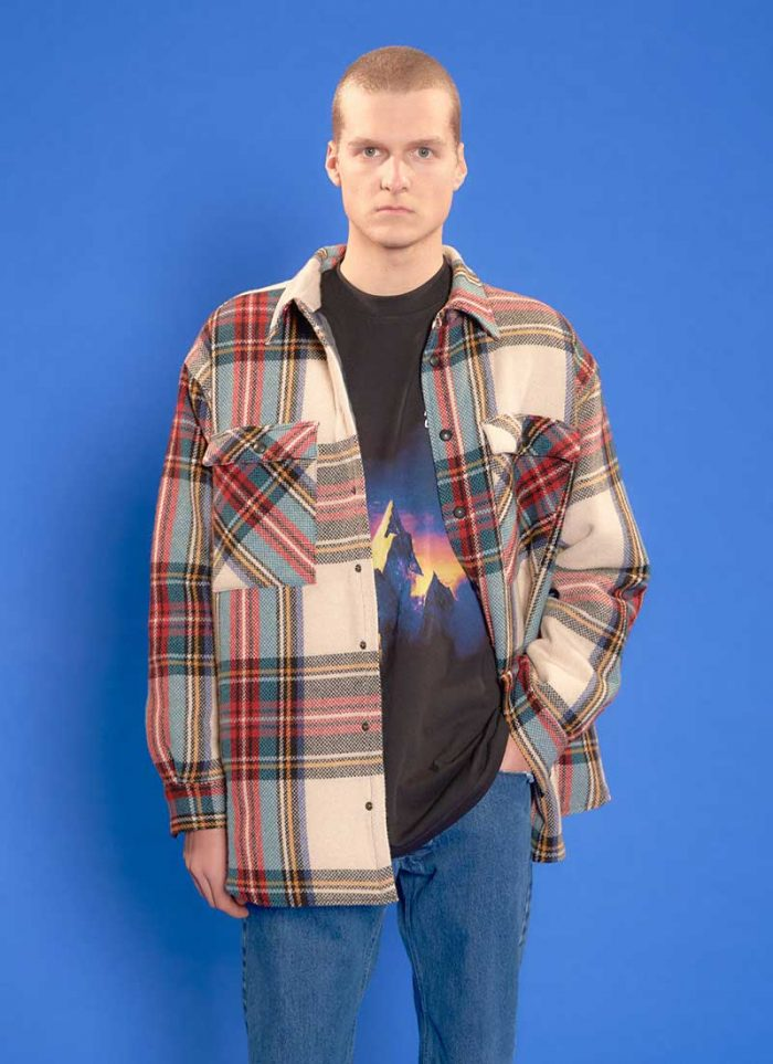 The model wears a total Bonsai look with a checked shirt, a t-shirt with a print, jeans