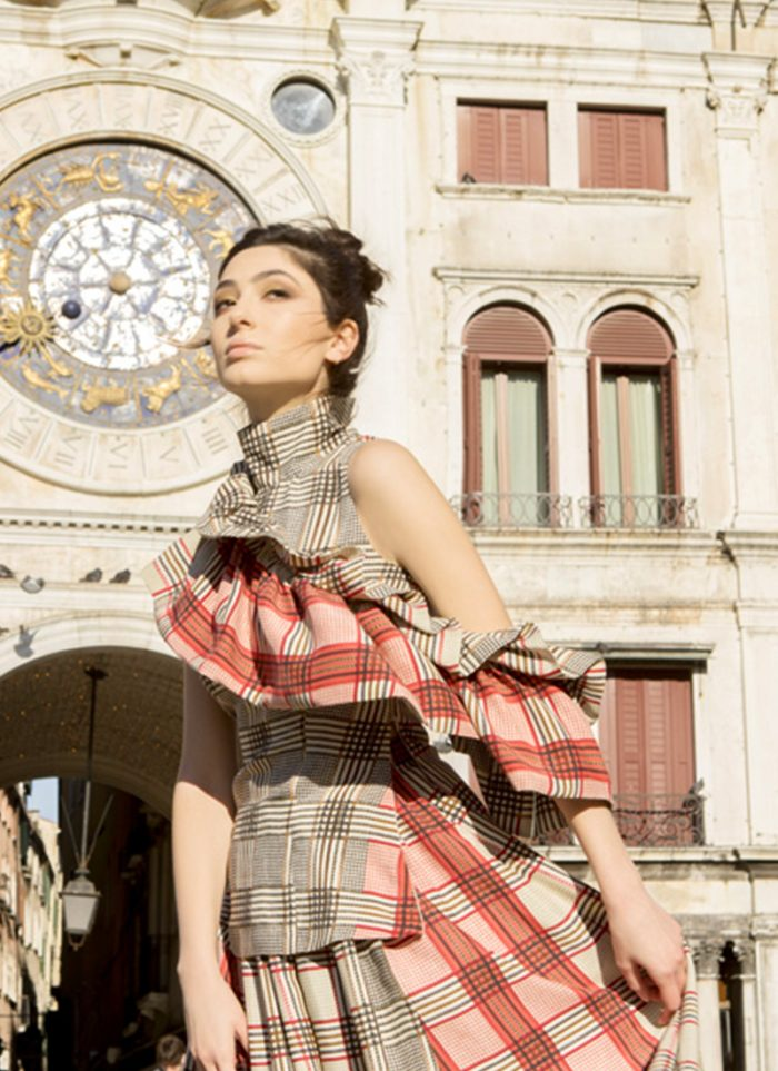 Model with CO-GO dress, high neck tartan beige pink red gray print with shoulder cut and ruffles