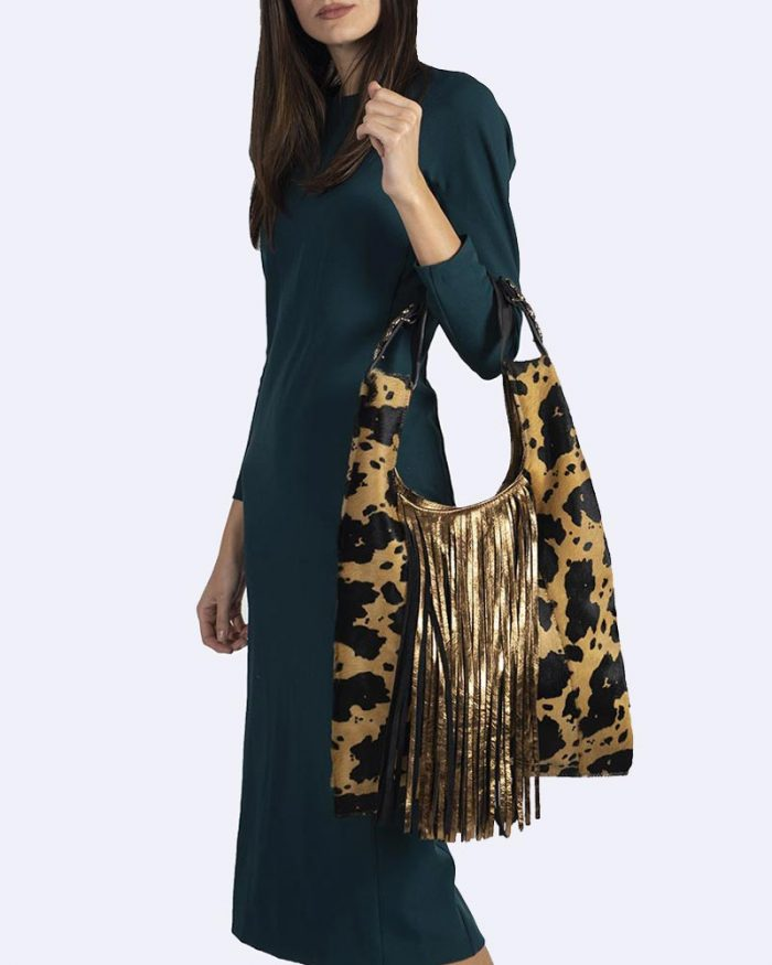 Model wearing spotted print maxi bag with Ecletta gold fringe detail