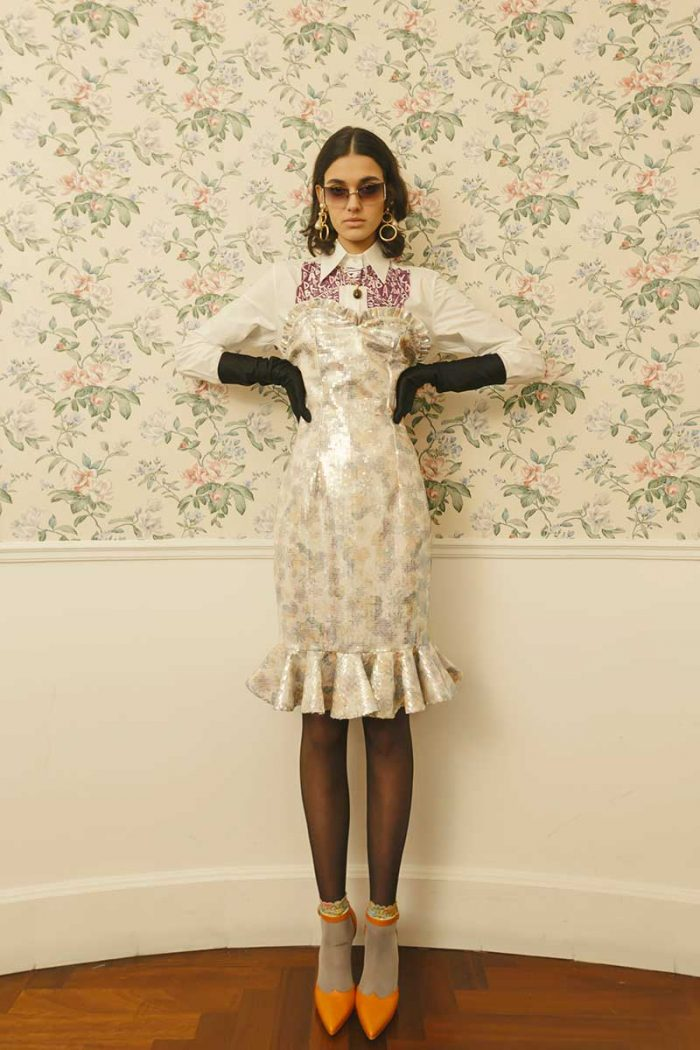 The model wears a total outfit by Gentile Catone white long sleeves shirt with central design detail, over the sweetheart neckline short dress with pleated details, laminated fabric and pleated skirt hem, black stockings, orange neckline with socks, long black gloves