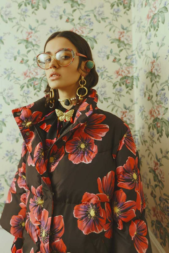 Half-length photo with a model wearing a coat and shirt Gentile black Cato with red and purple flowers, large round glasses, long and geometric earrings with a gold-necked butterfly-shaped brooch and a round stone necklace