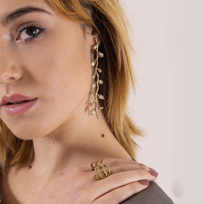 Model wears long earring in the shape of leaves by Giorgia Panzironi