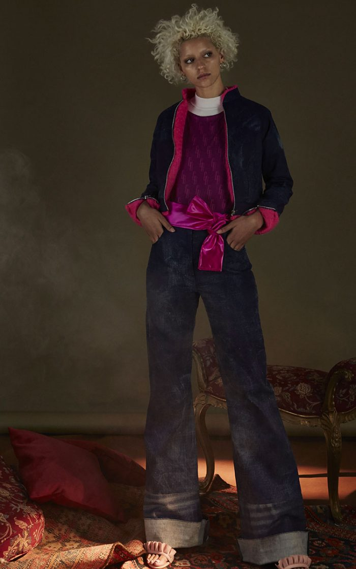 The model wears mini bomber jackets in pink inner denim and wide denim trousers, a purple GA branded sweater and a white turtleneck