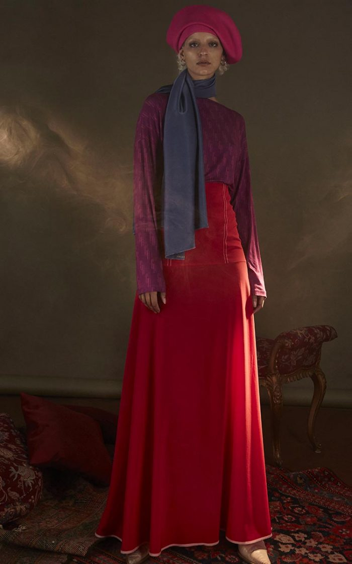 The model wears a large purple multi-logo sweater, a long red flared skirt, a pink hat and an indigo scarf