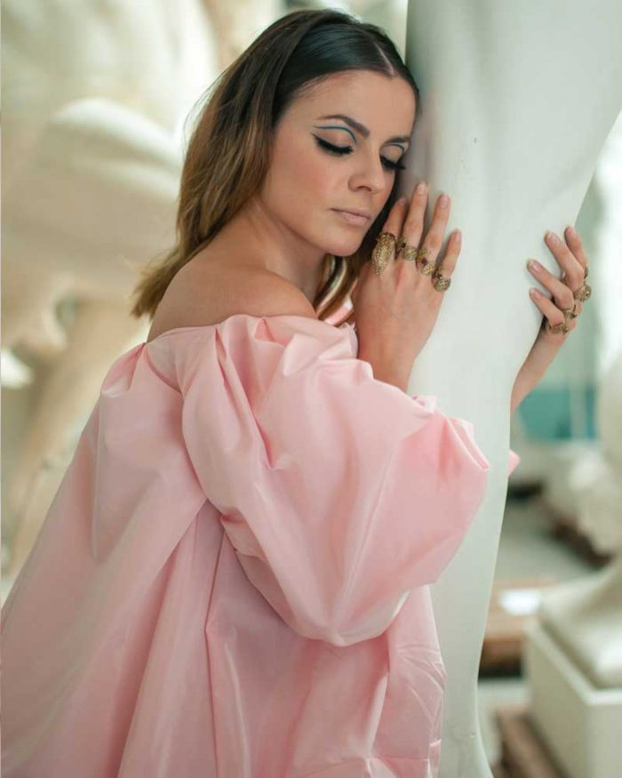 Model wearing a pink dress and rings in yellow bronze with a leaf motif from the Live Lives collection by Giorgia Panzironi Jewels