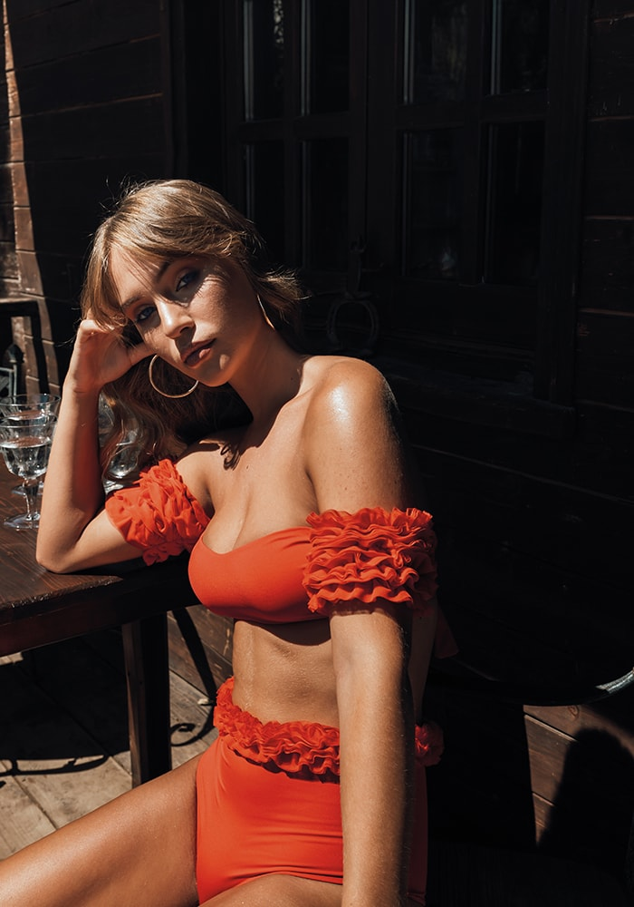 Model wears orange bikini Kinda 3D Swimwear with tulle band and straps and high waisted coulotte with tulle band
