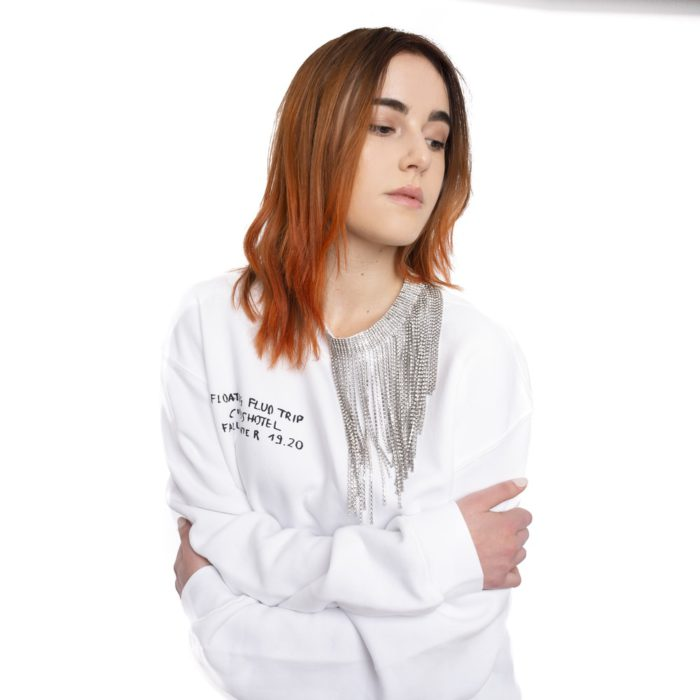 white sweatshirt with circus hotel lettering and metallic fringes
