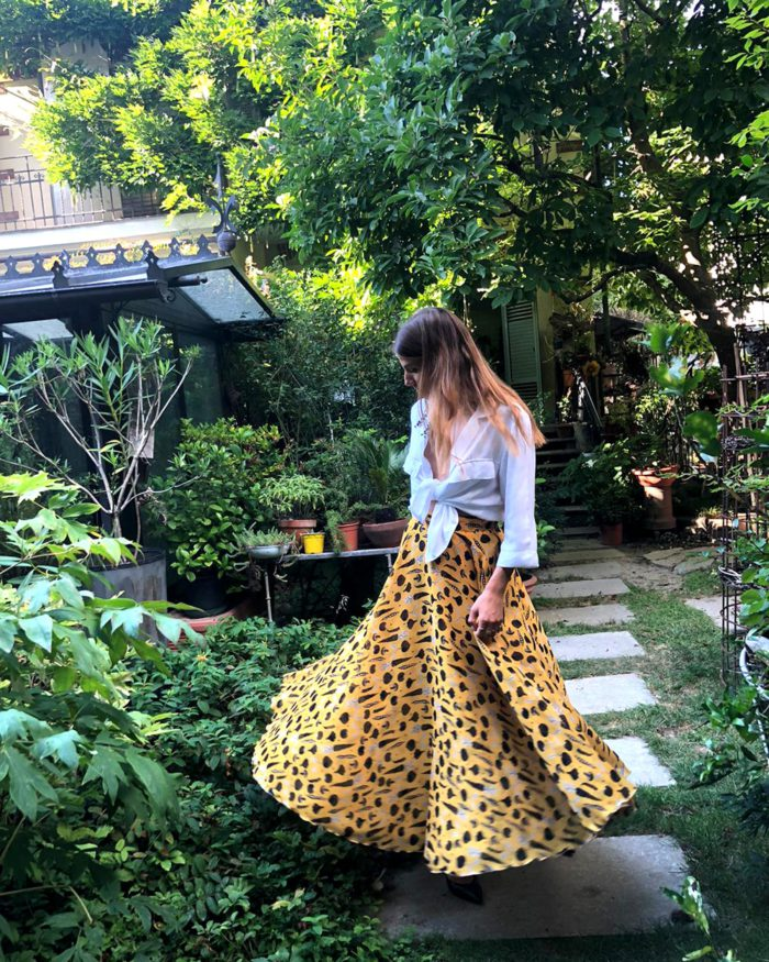 model wears white blouse with printed yellow maxi skirt