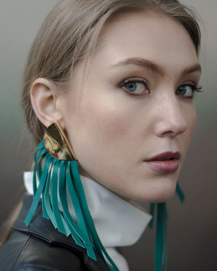 Close-up model with My Golden Cage earring with green leather fringes and 24k light gold plated brass