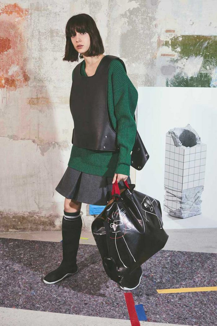 sweater by PLAN C: the model wears a dark green oversize sweater combined with a overlaid vest in black leather and a gray miniskirt