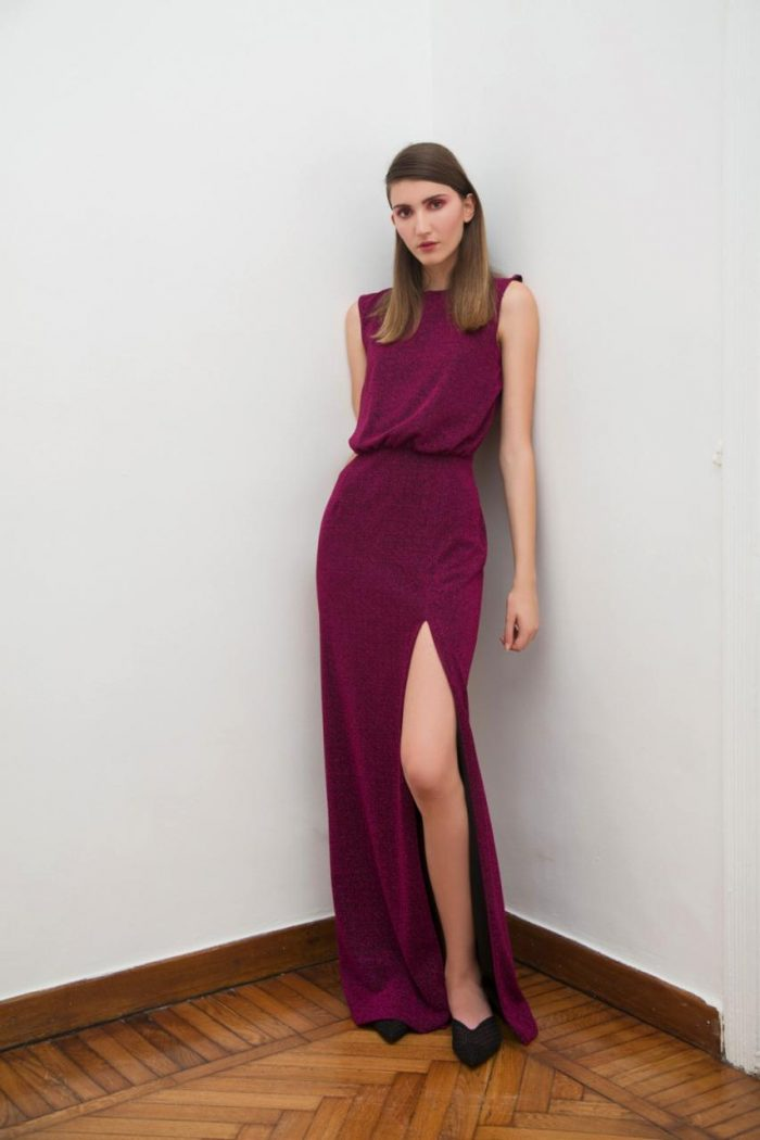 The model wears a long burgundy dress with a slit