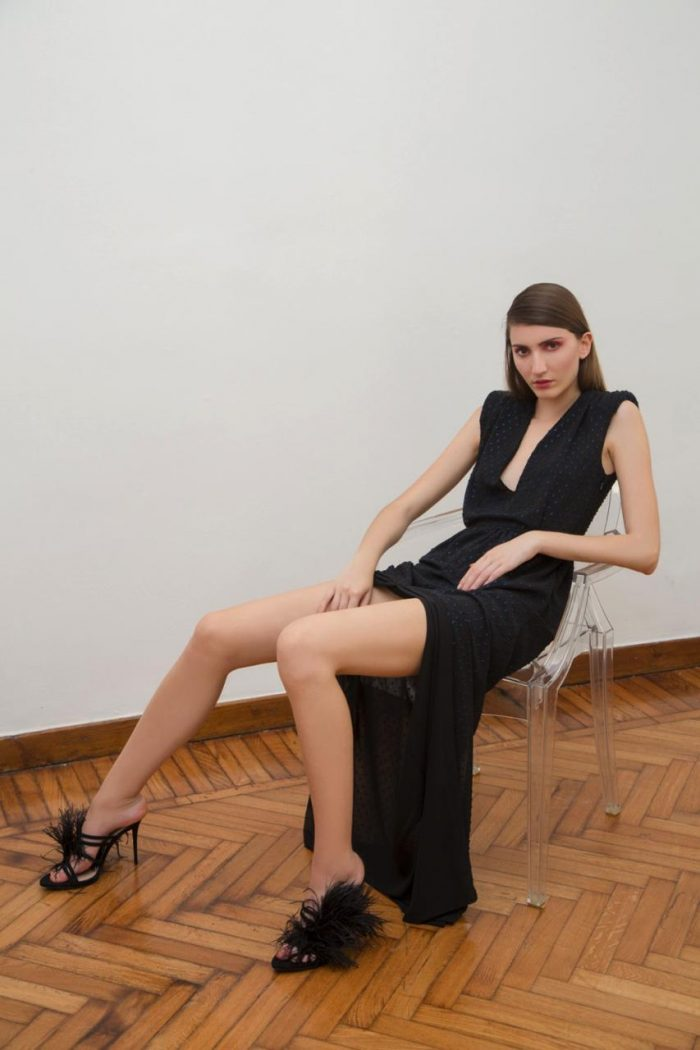 The model wears a long black dress with a slit and a deep neckline