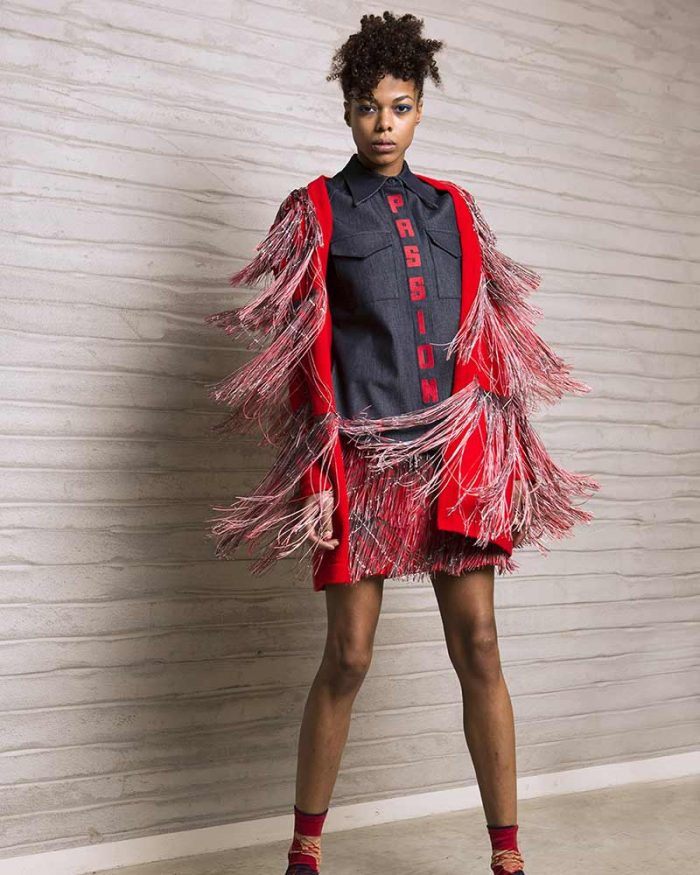 Model wears Tiziano Guardini suit, red jacket and mini skirt with fringes and denim shirt