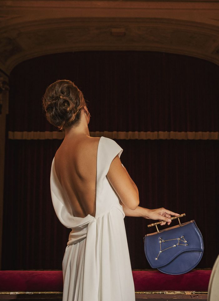 Leather Handbag by Villa Trentuno with a semi-arch shape, blue with a gold metal handle that emulates a twig detail