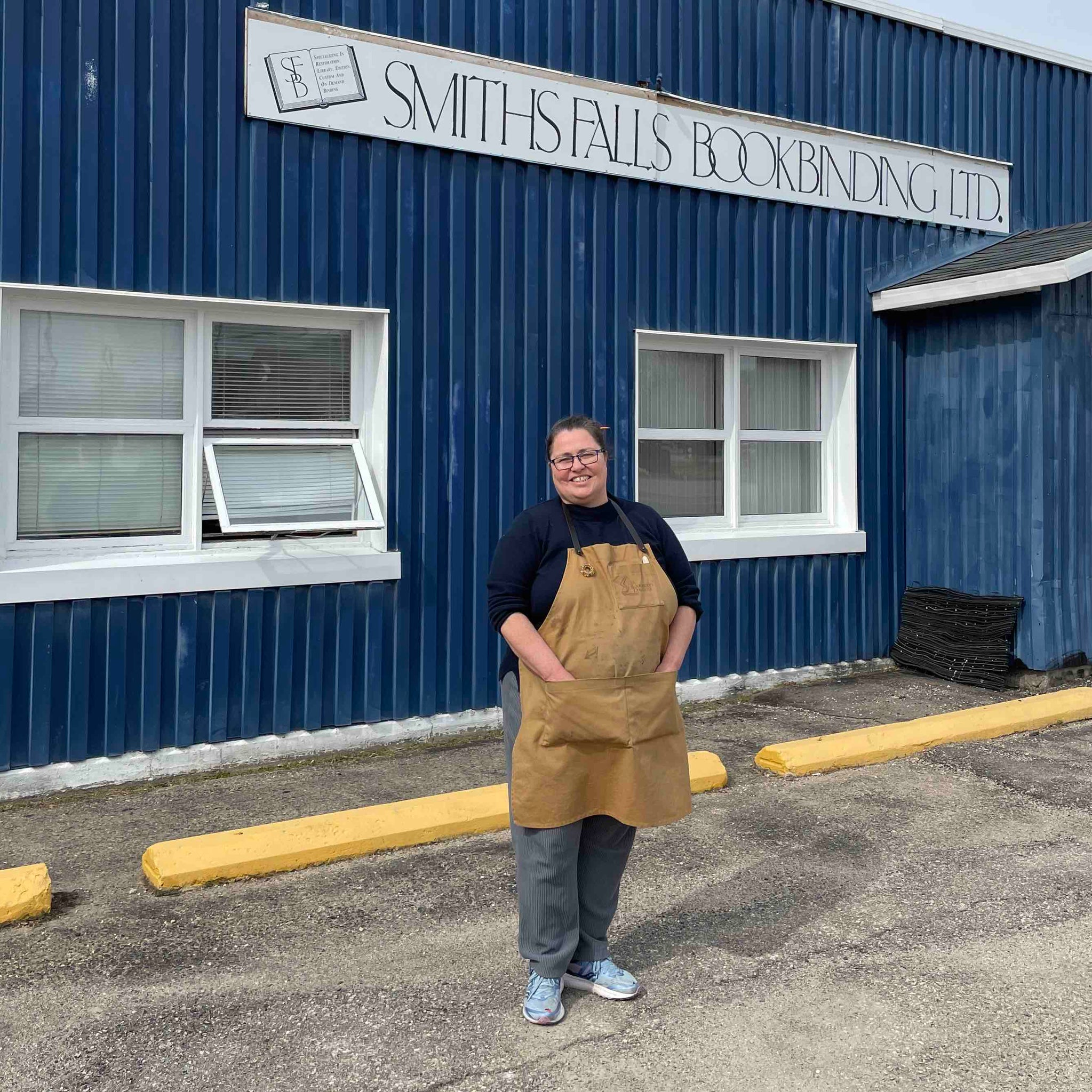 Laura Front of Her Shop In Parking Lot Windows Smiths Falls Bookbinding Blue Building