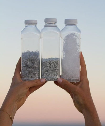 hands holding three glass bottles filled with rocks against a pink and blue sky