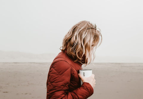 outdoorsy woman on beach with reusable cup