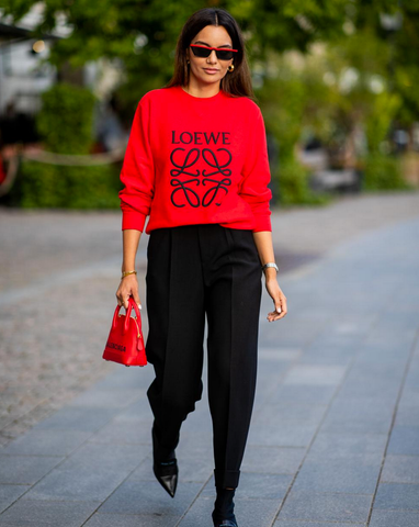Woman wearing bright red shirt with big Loewe logo on it