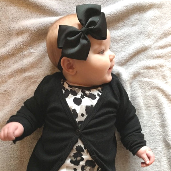Mila wears our black large butterfly bow baby headband