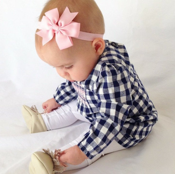 Isla wears our PAIGE pinwheel baby headband
