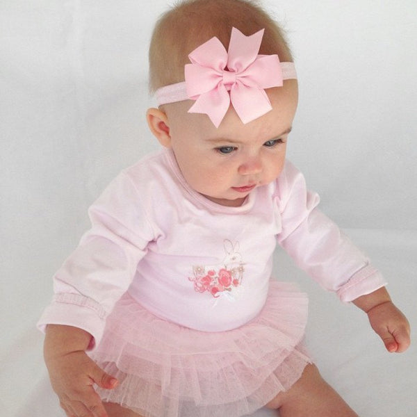 Isla Rose wearing our Paige pink pinwheel stretchie baby headband