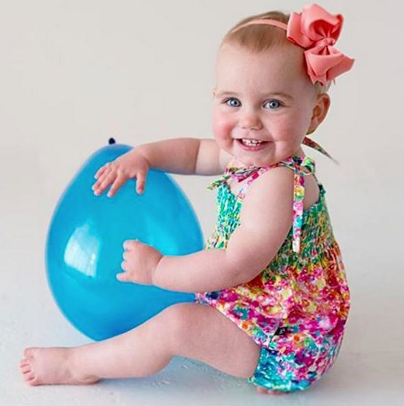Isla Rose playing with a balloon wearing a Pretty Little Clippies Australia Cassidy Coral Trixie bow headband