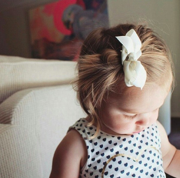 Cute toddler wearing ivory baby bow hair clip (by Pretty Little Clippies Australia)