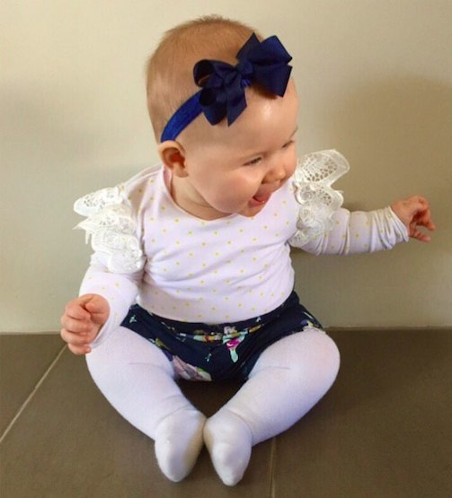 Navy Stretchy Baby Headband modelled by gorgeous happy baby (Pretty Little Clippies Australia)
