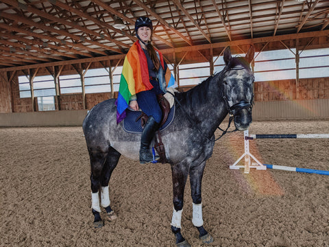 horse and rider with progress pride flag worn as cape