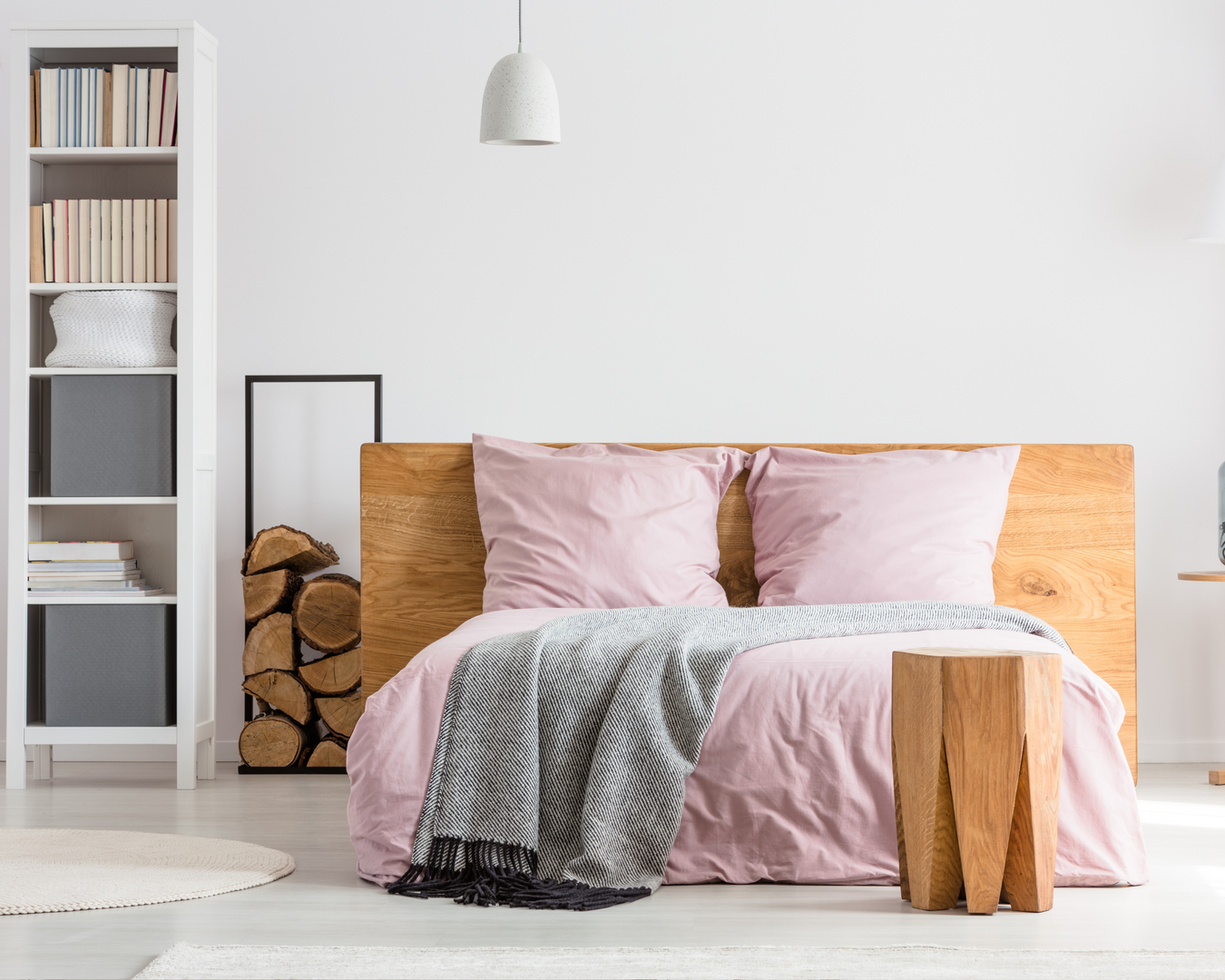 Pink bed with chopped wood and white bookshelf