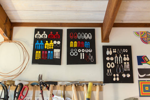 Pops of primary color powder coated earrings hanging on the wall in Liz's studio, ready to be taken to the Virginia Museum of Fine Art for the Yves Saint Laurent exhibit.