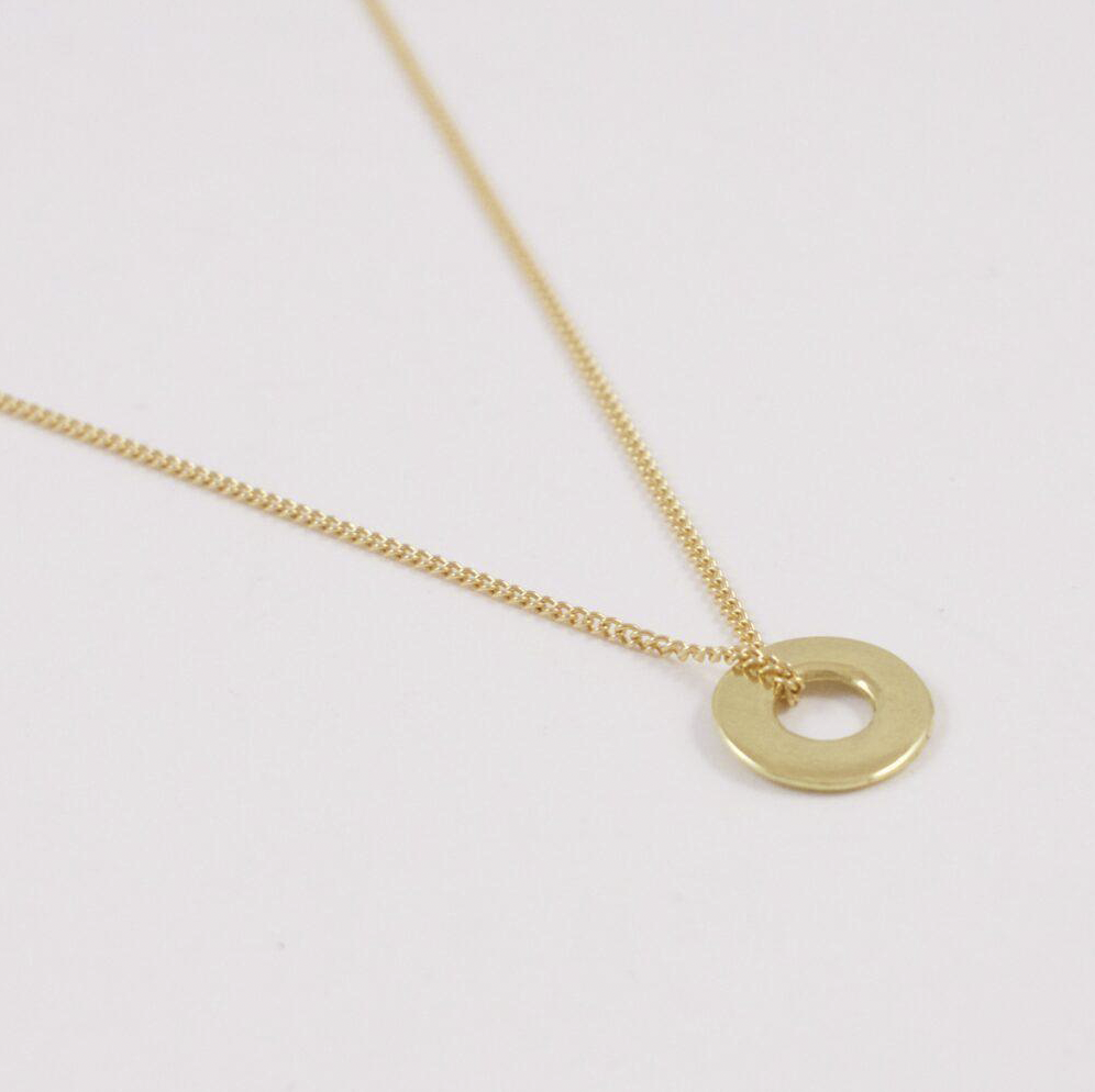 The Mini Ina 18 karat gold necklace lain flat. This close up shows the tiny sculptural disc and the delicate way the chain wraps around it.
