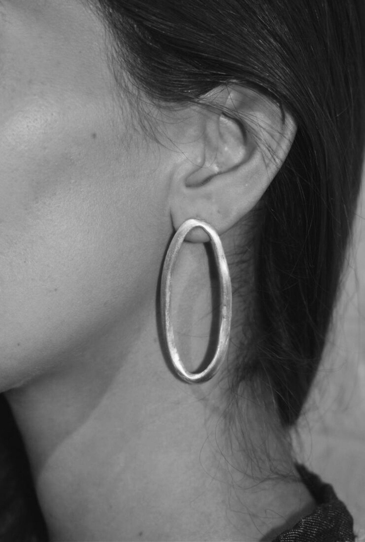 Image shows the Organic Oval Earrings on a model for scale.