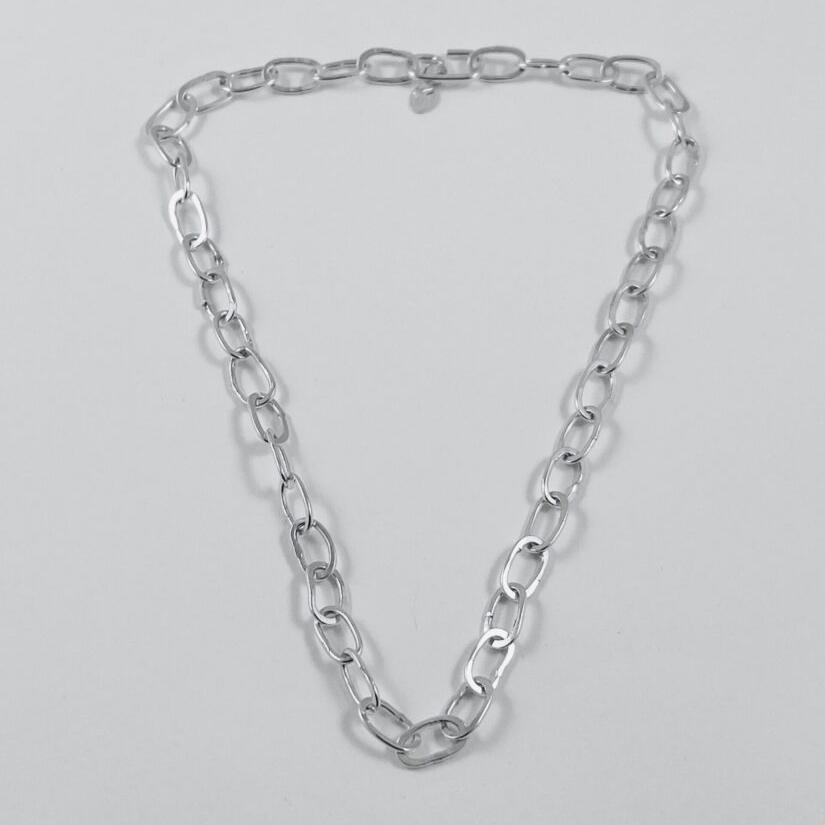 A flat lain photo of the petit oval chain that shows well the wabi sabi aspect of each of the hand formed links.