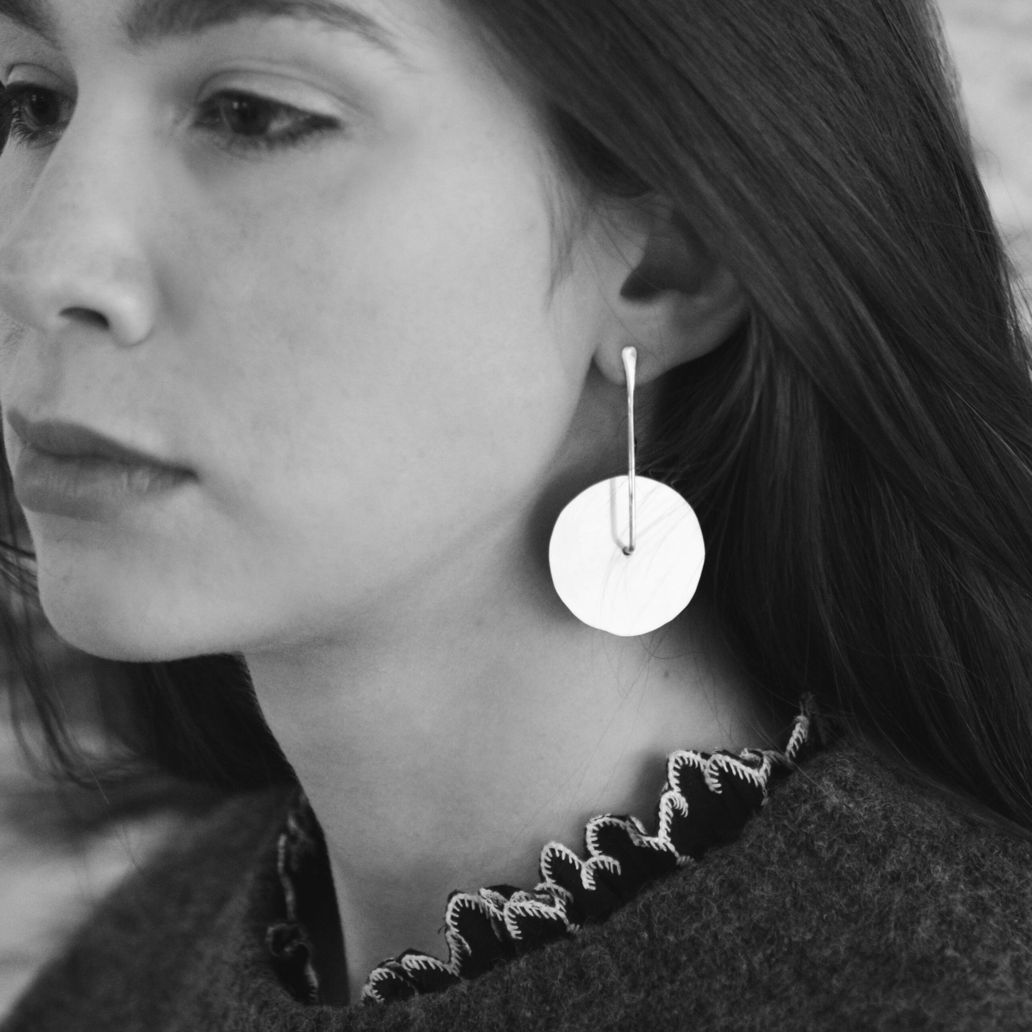 Image shows large size twirling disc earrings on a model for scale.