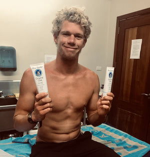 John John Florence holding 2 tubes of Blue Healer Care cream