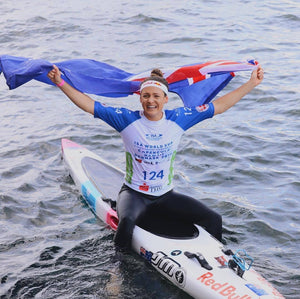 Jordan Mercer, Surf Ironwoman SUP Champion Red Bull Athlete with Australian flag after winning the ISA World Sup Competition with the Australian team