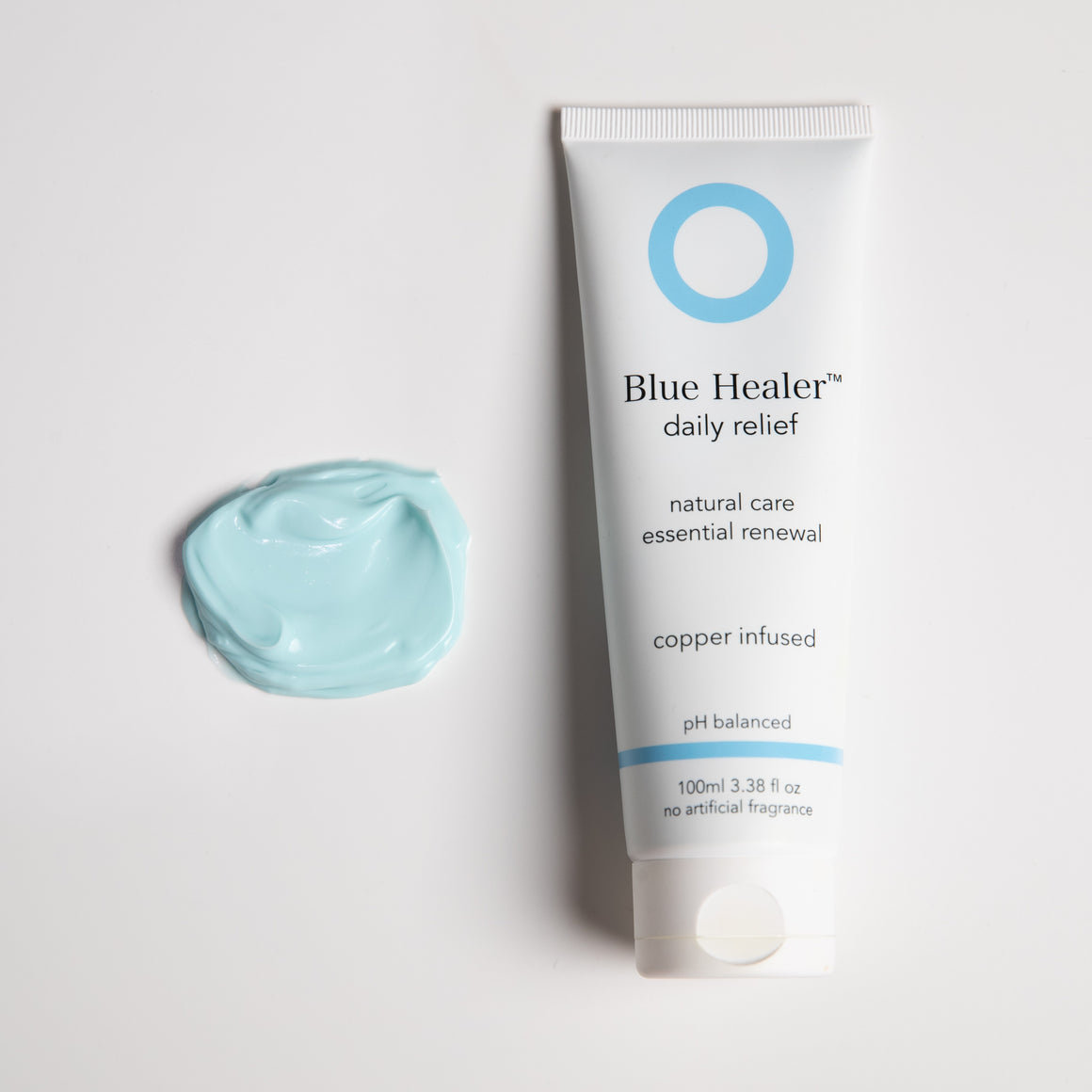 Blue Healer daily relief product tube next to a dollop of the naturally blue coloured cream.