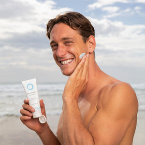 Ali Day World Ironman champion of 2019 applies Blue Healer Daily Relief cream to his face while standing at the beach after-sun.
