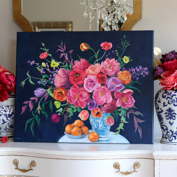Elizabeth Alice Studio large painting of a flower bouquet in chinoiserie vase sitting on furniture, red orange purple flowers in blue and white vase with navy background