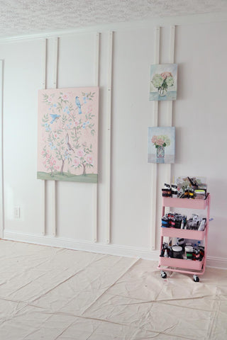 Wall easel artists peg wall by Elizabeth Alice Studio with chinoiserie paintings and pink craft cart dropcloth