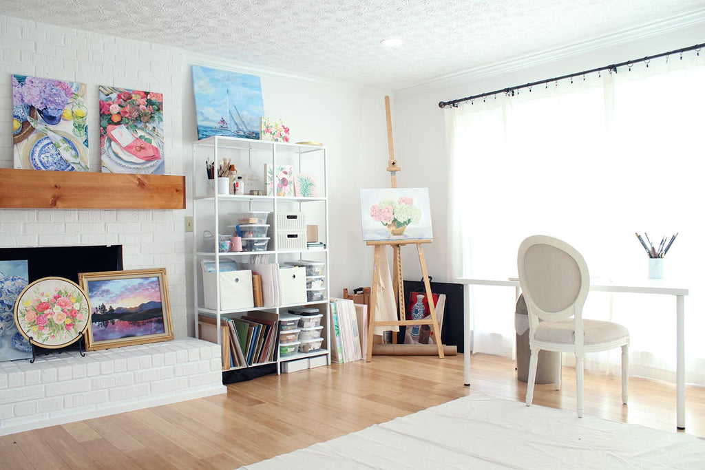 White bright artist studio by Elizabeth Alice Studio, artist's office with table, shelves, easel, and white drapes