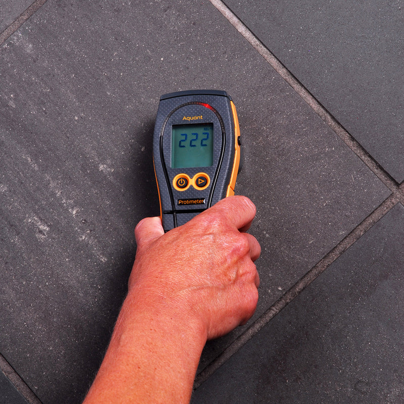Protimeter Aquant Moisture Meter being used to measure moisture in flooring