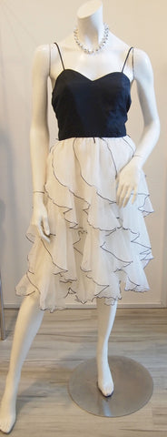 Black top with white ruffles and black trimming skirt