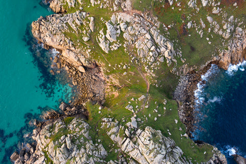 Top down view of tourquoise sea in Cornwall either side of a spit of land in sunshine